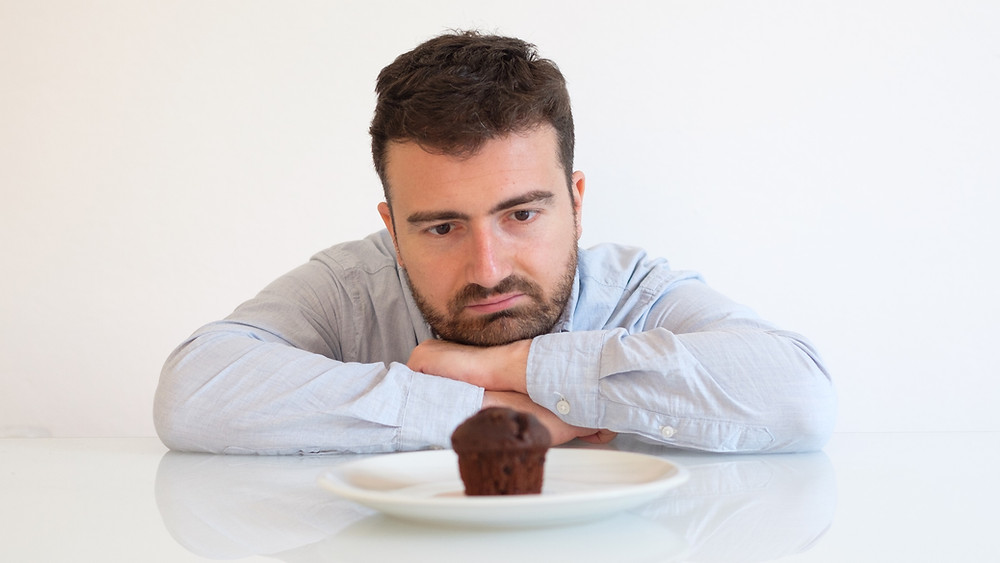 A man staring longingly at a muffin