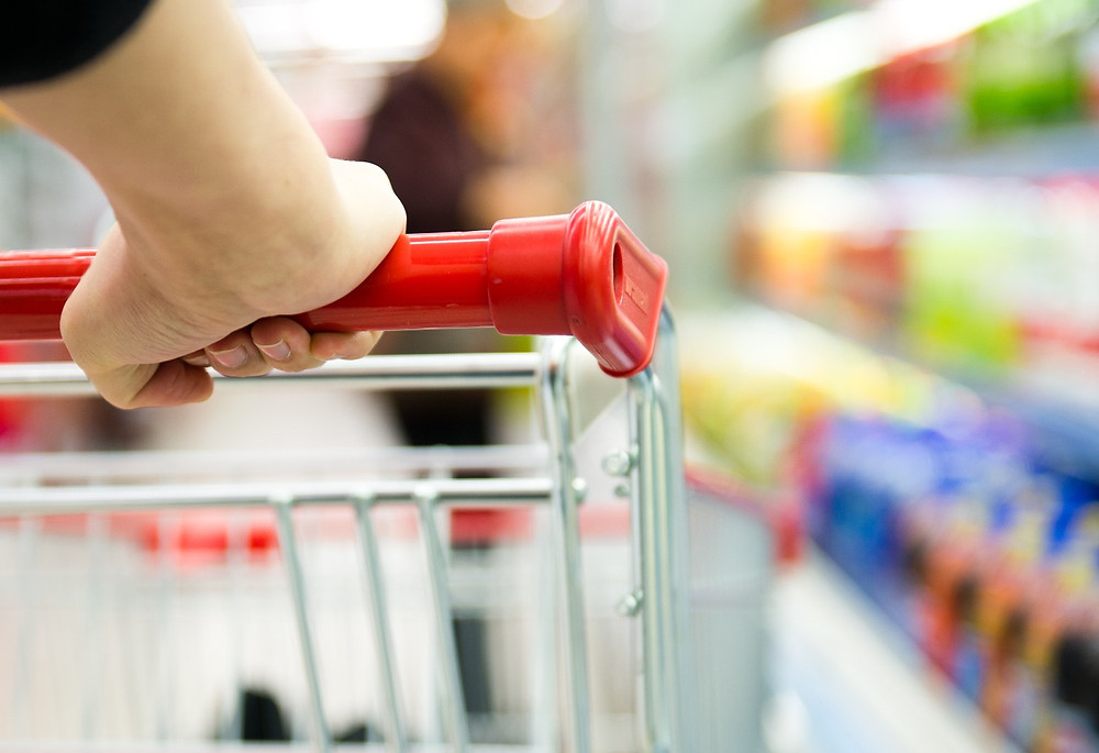 Closeup of a hand pushing a supermarket trolley