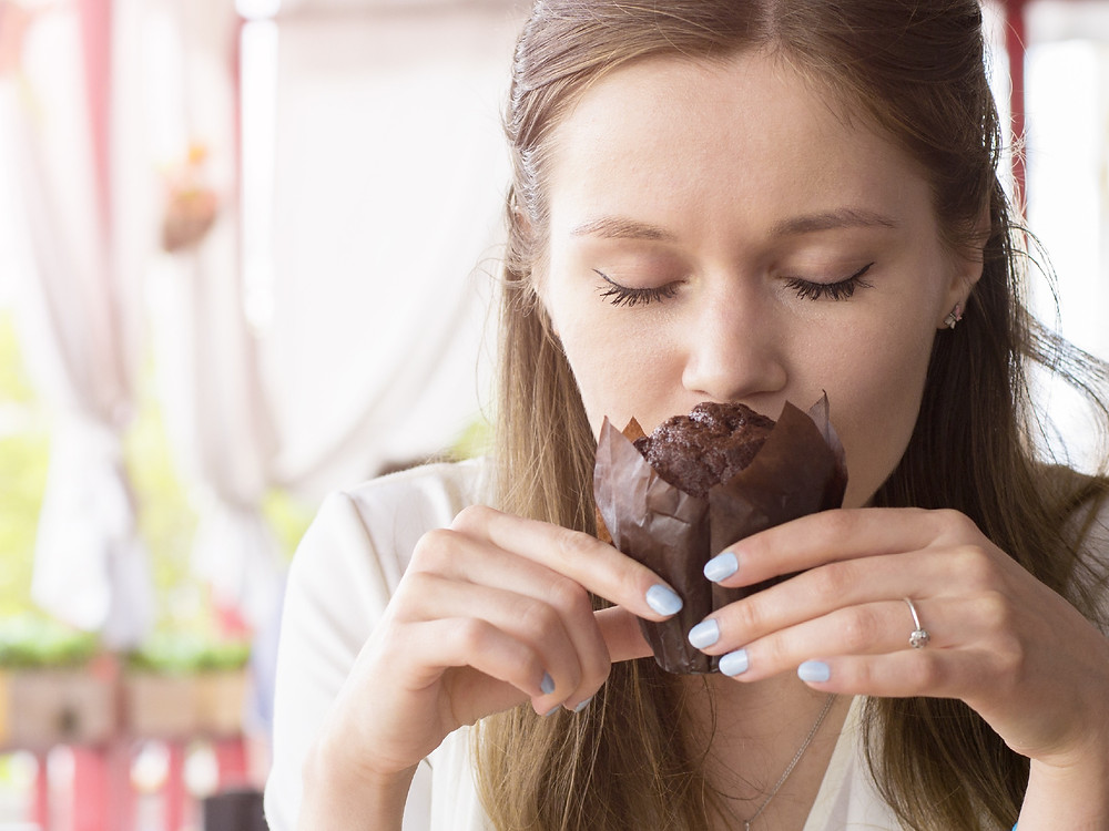 Woman smelling a chocolate muffin