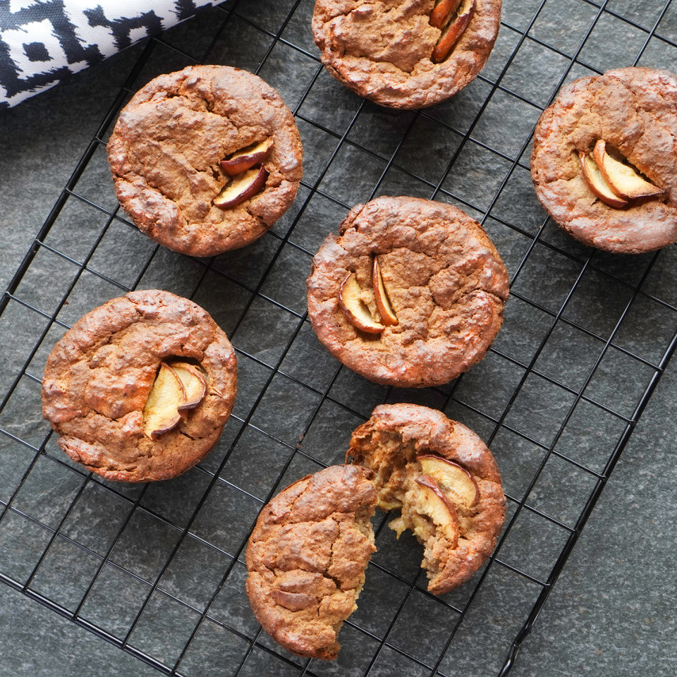 Warm apple and oat muffins cooling on a wire tray
