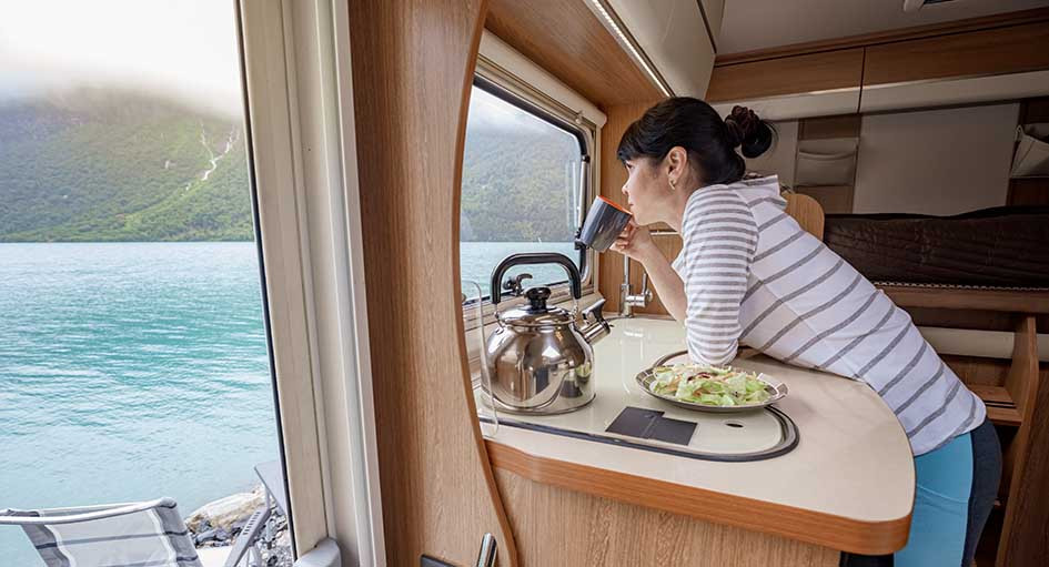 Woman looking out of a rental motorhome in Ireland