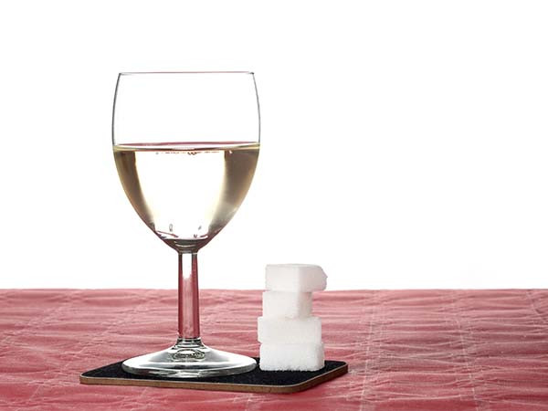 A glass of white wine with sugar cubes next to it