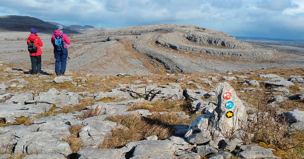 Two hikers on the Burren following coloured arrows