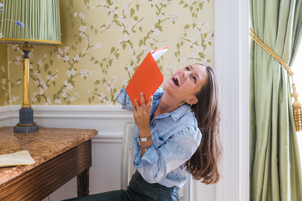 orange leather notebook held by laughing girl