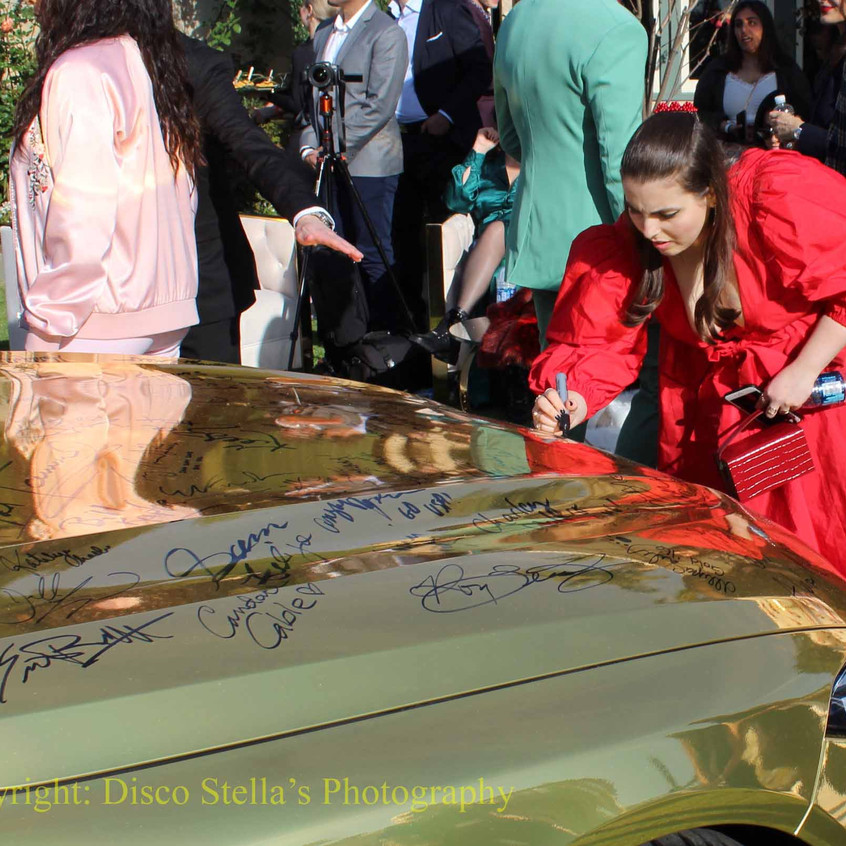 Beanie Feldstein signing car
