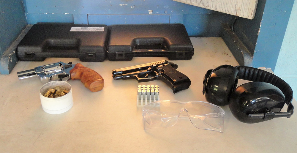 A pistol and revolver on the bench with safety equipment and ammo