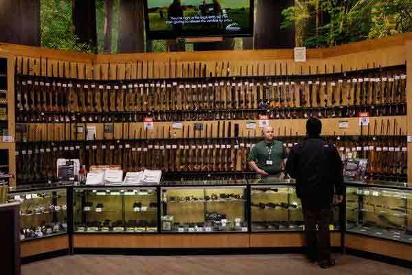 Individual standing at a gun store counter with salesperson