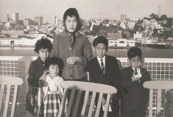 1963–Oy Mui Chen (husband San Hon Chen taking photo) and her four children arriving by ship in San Francisco. The smallest girl is my mother.