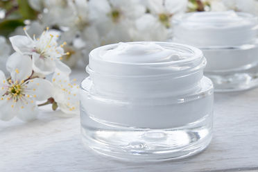 A jar of cream close-up, face cream surrounded by cherry flowers. Face Cream in Glass Jar.