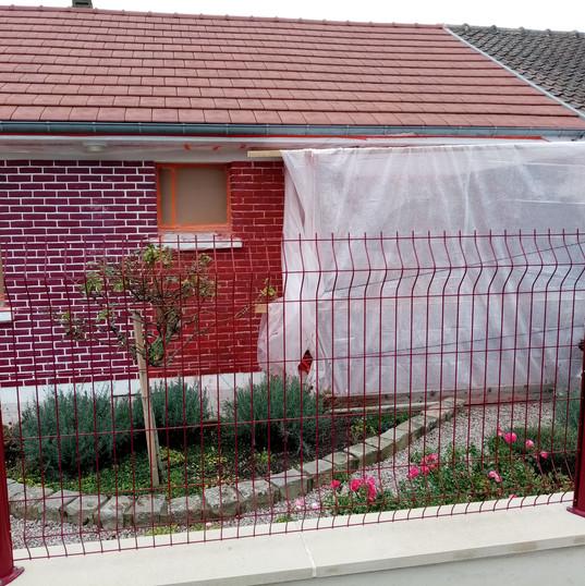 décapage peinture rouge et blanche sur façade en brique
