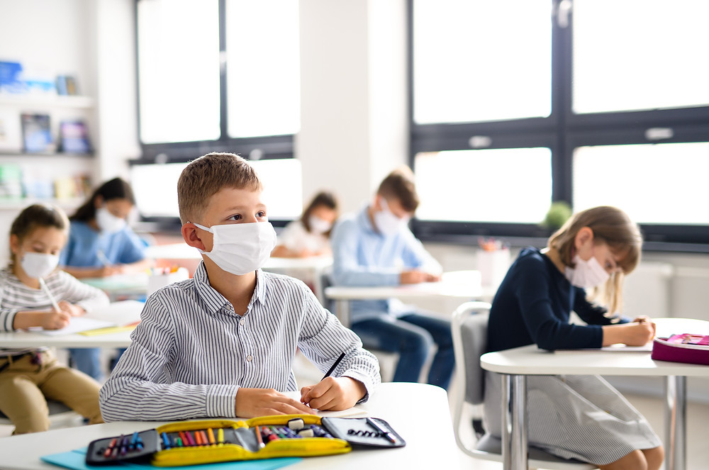 Students sit in class wearing a mask to prevent the spread of COVID-19