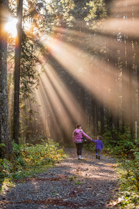 A woman walking with her child in the woods