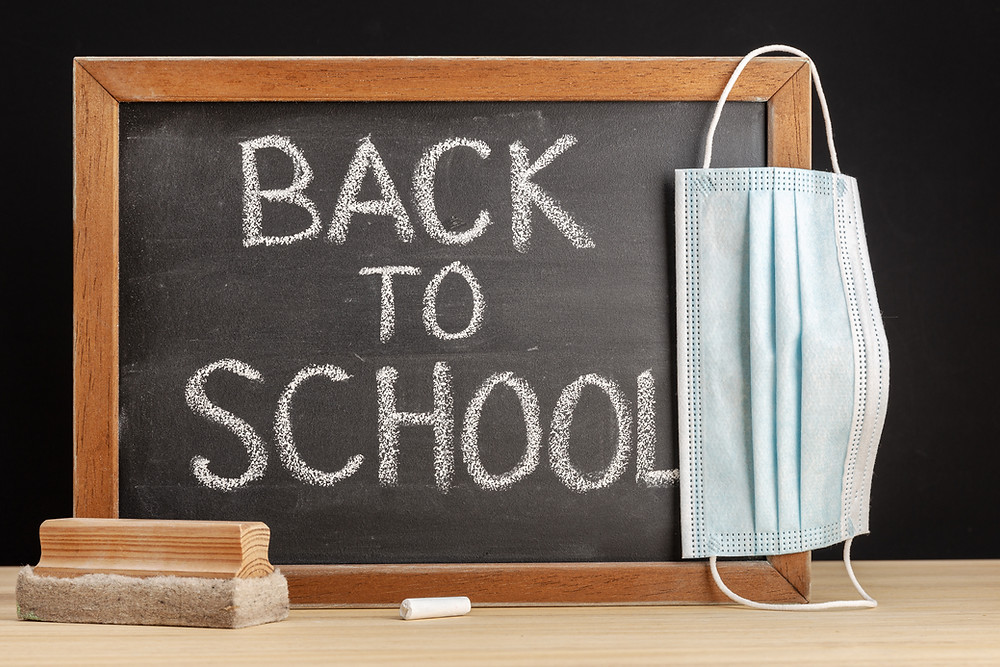 "A chalkboard with a mask hanging on it reads ""Back to School"""