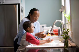 A caregiver and child washing their hands