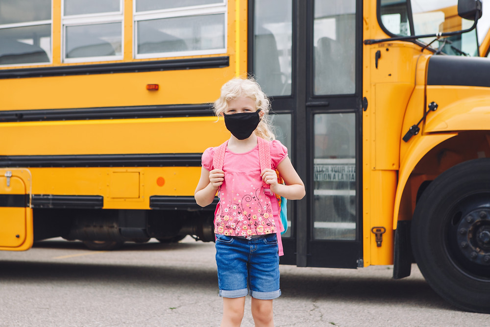 A student with a mask stands in front of the school bus