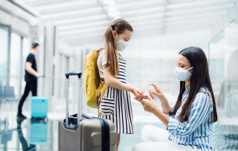 Mother and Daughter with face mask disinfecting their hands in the airport