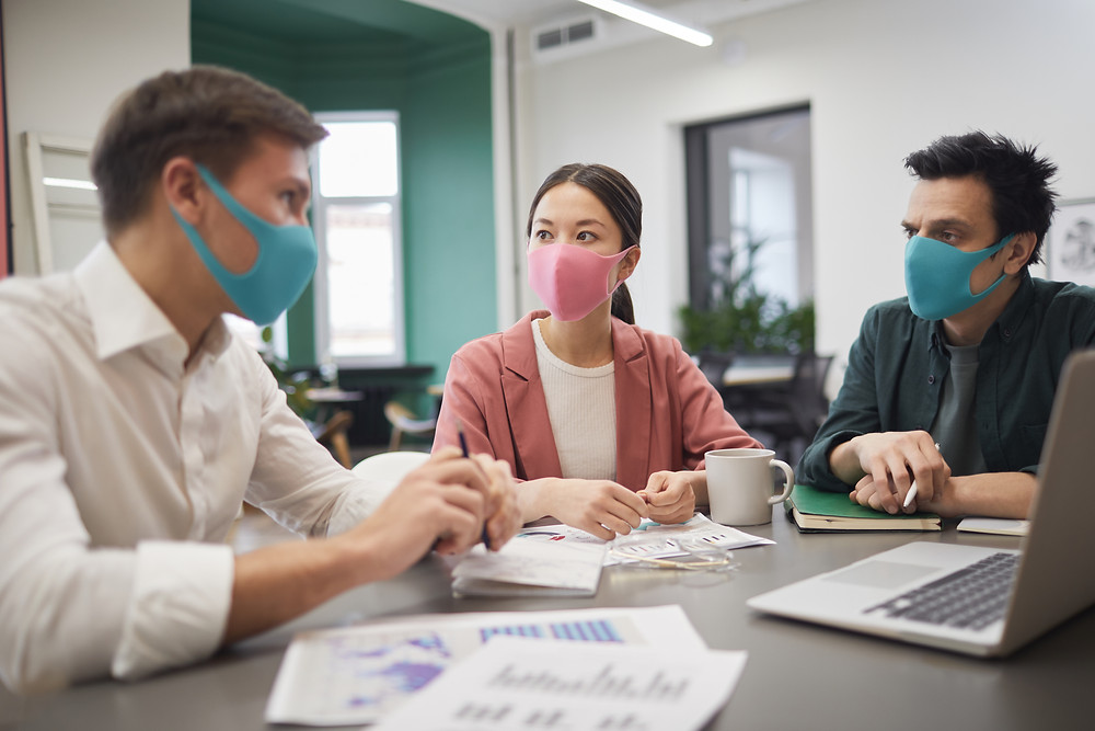 Co-workers wearing masks in the office to protect themselves and others from Coronavirus.