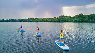 active-family-sups-standing-up-paddleboards-river-water-summer-family-sport-aerial-top-vie