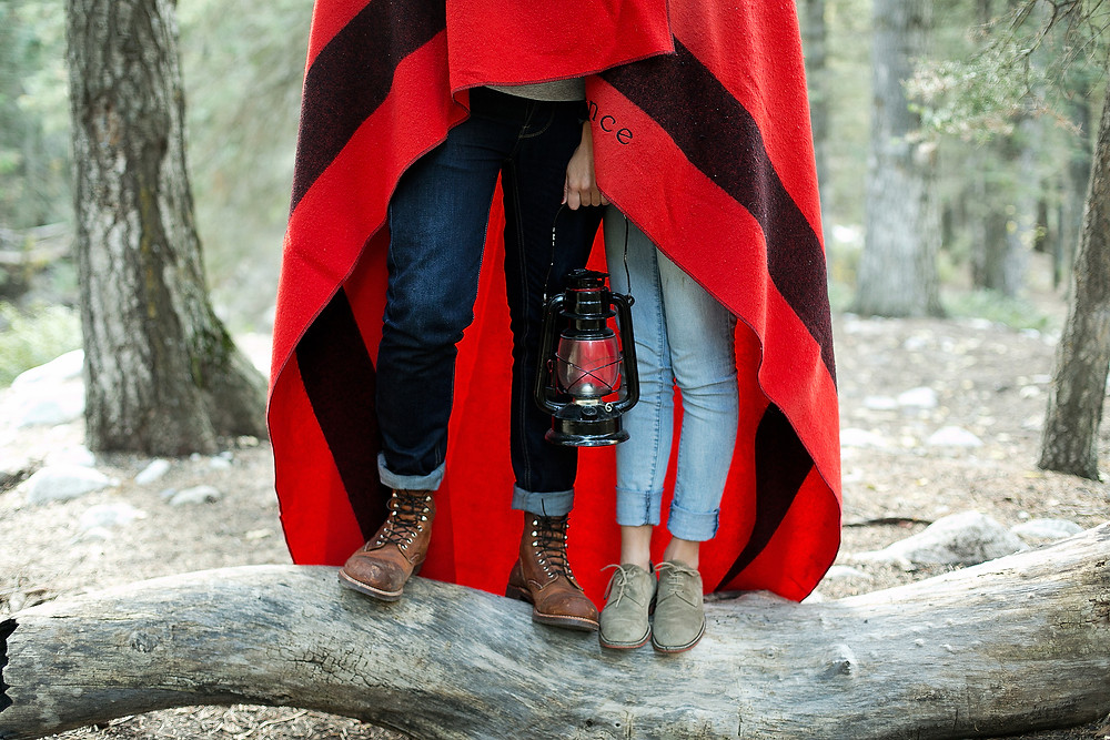 boy and girl wrapped in blanket holding lantern in middle