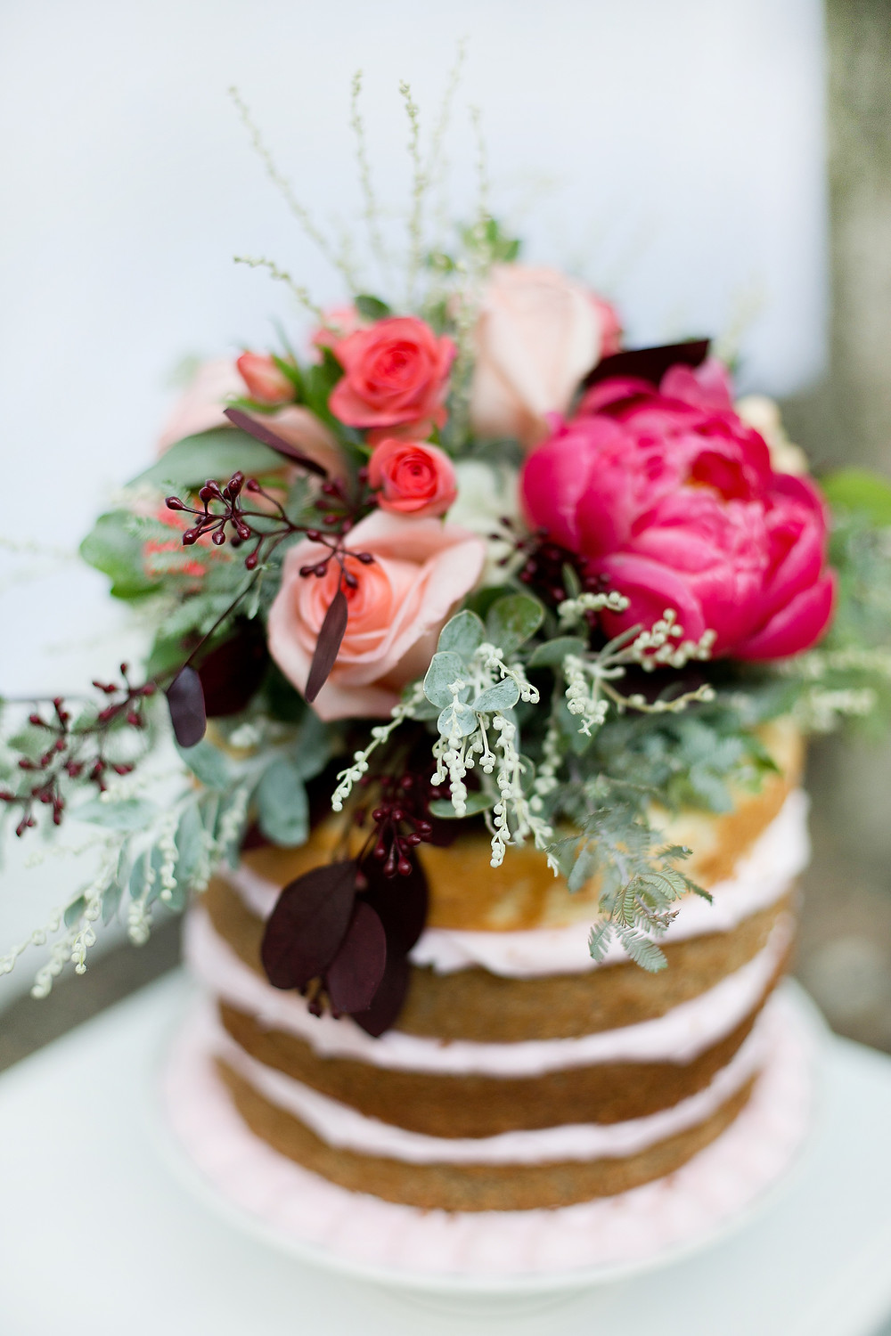 close up of flowers on top of wedding cake