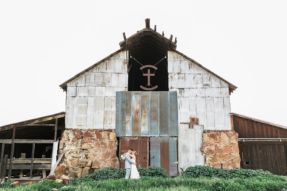 bride and groom behind barn