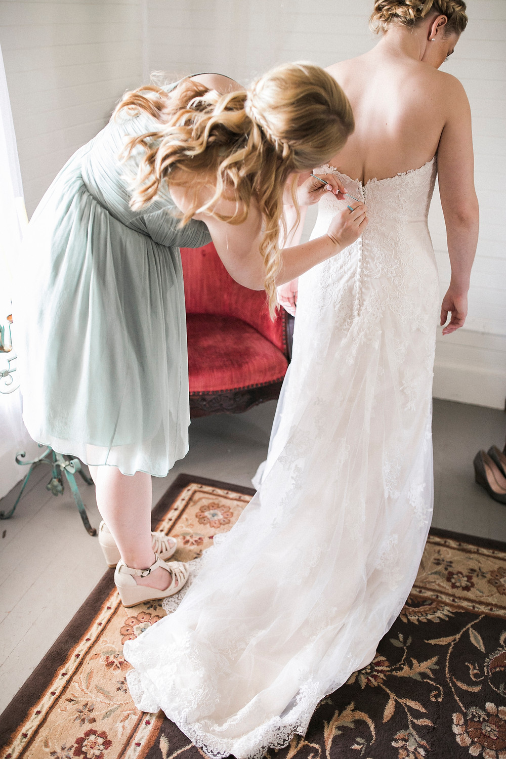 sister helps bride into dress