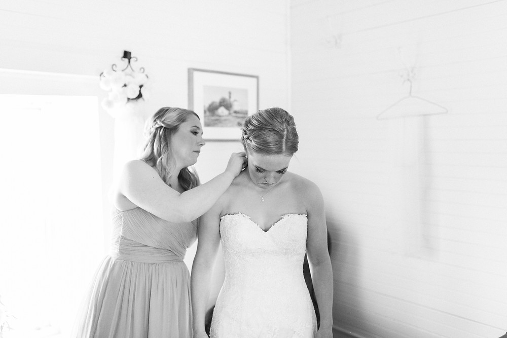 sister helps bride with necklace