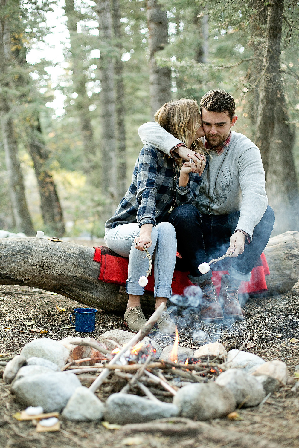 boy has his arm around girl at campfire roasting marshmallows