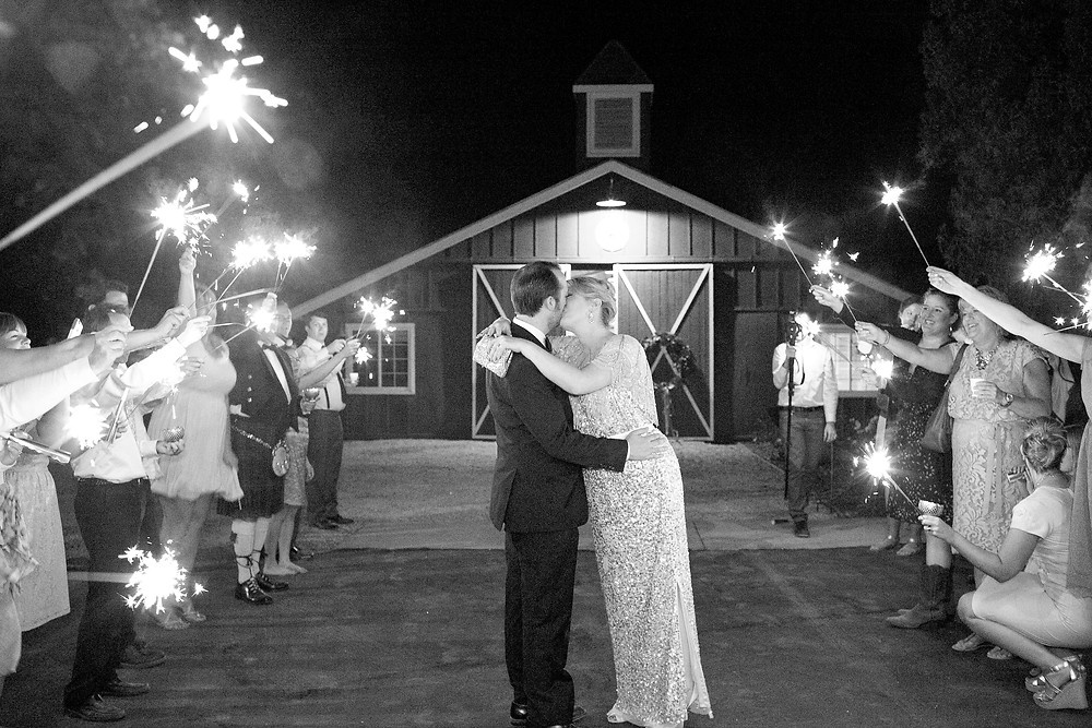 bride and groom exit with sparklers at night