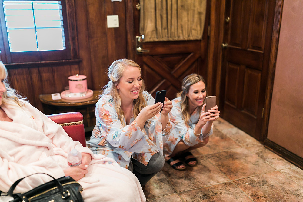 bridesmaids take photos of bride