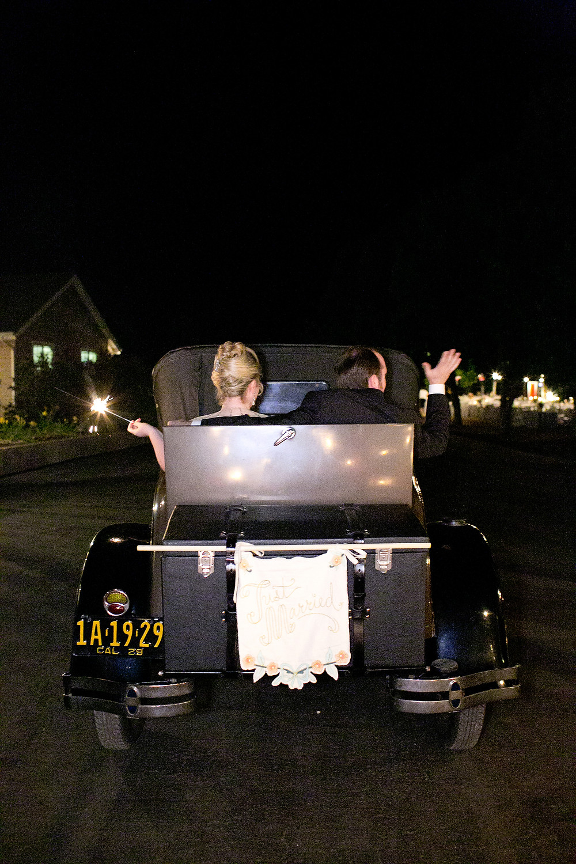 bride and groom leaving in a vintage car
