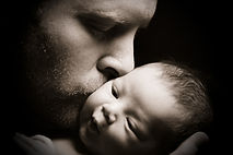 Father kissing newborn during paternity leave