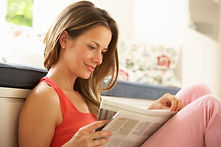 Woman Relaxing With Newspaper At Home.jp