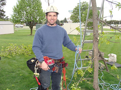 Daniel Haas standing by a tree holding a rope getting ready to trim the tree