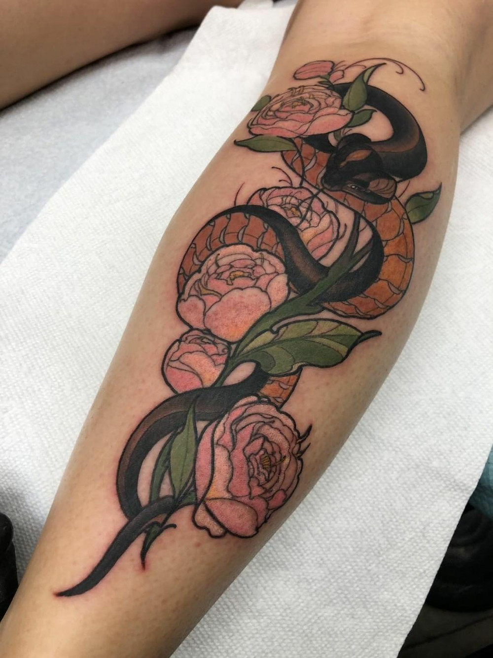 Snake and floral tattoo by Justin Tauch.