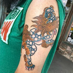 Foo dog tattoo on upper arm, one of the beautiful tattoos done by Tan Vo in Long Beach.
