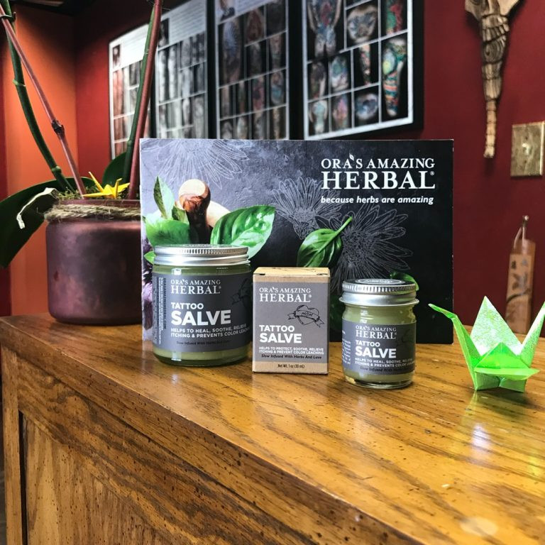 Jars of Ora's Amazing Herbal Tattoo Salve on the wooden counter of Paper Crane Studio in Long Beach, CA, part of our aftercare routine to help your tattoo age beautifully.