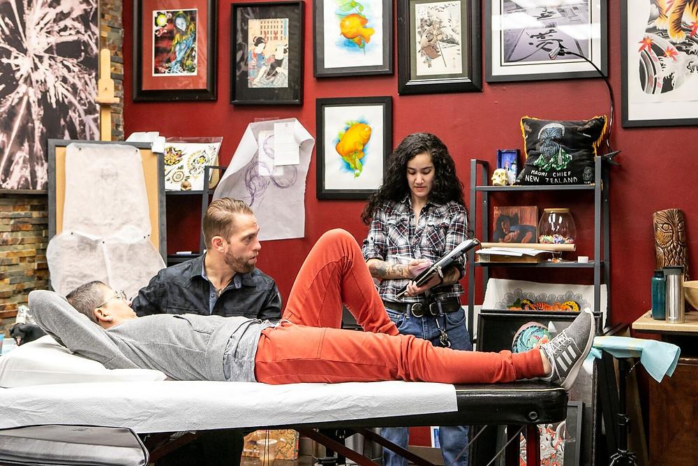 Senior artist Mikey Vigilante helps apprentice Jackie Siu with a tattoo design.