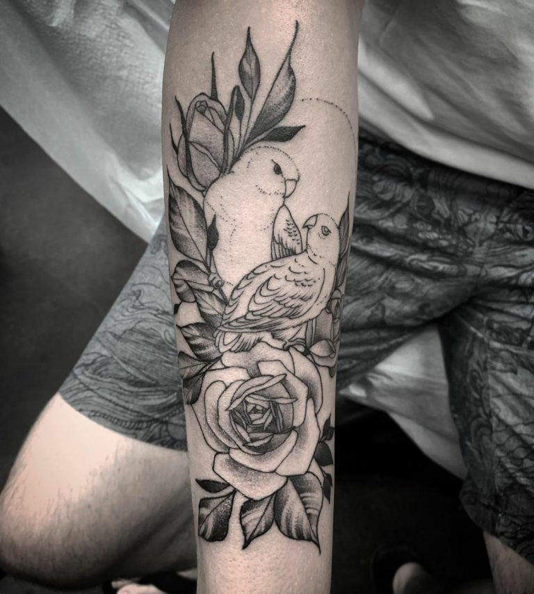 Two birds with roses blackwork tattoo by Jesse Iris on a client's arm.