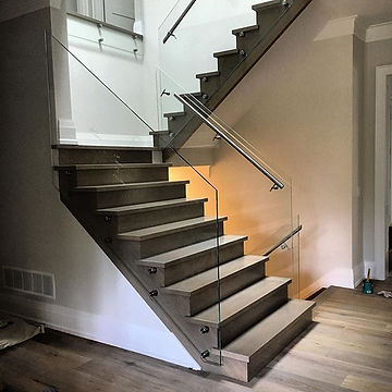 Beautifully stained staircase equipped with gorgeous glass railings at this custom build for _rockcl