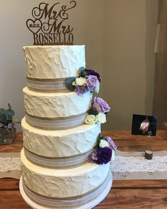 A sweet rustic wedding cake with burlap and lace adorned with fresh florals.jpg