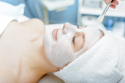 Woman having facial mask at beauty salon