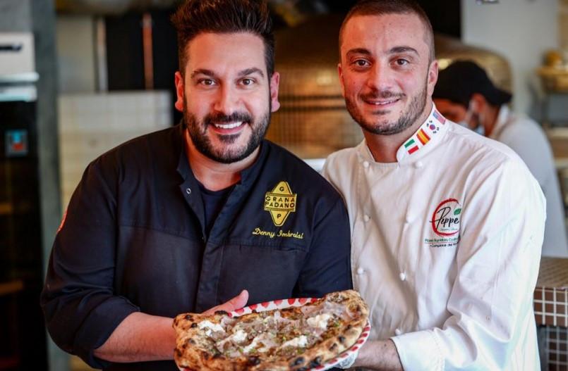 Denny Imbroisi et Giuseppe Cutraro en train de tenir une pizza entre leurs mains