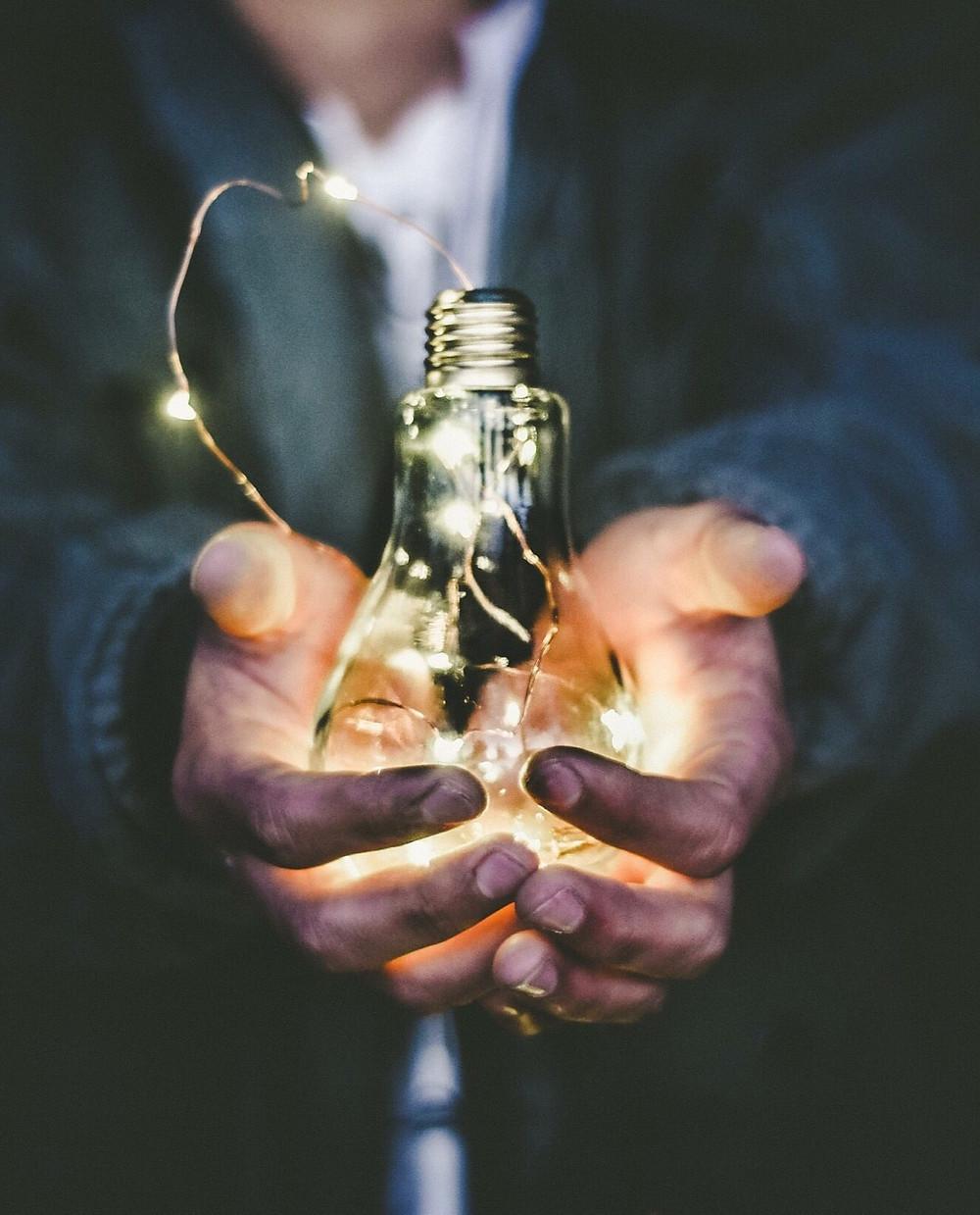 Ampoule éclairé dans la main d'un homme