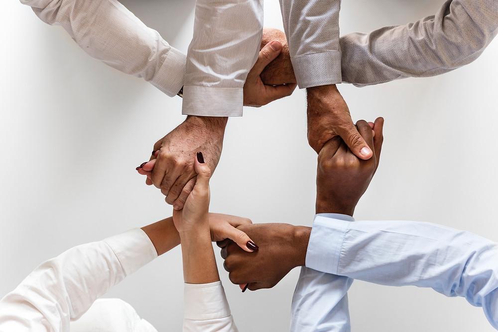 Mains croisées de quatre personnes