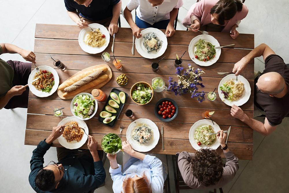 Table de restaurant avec des convives en train de discuter plusieurs plats
