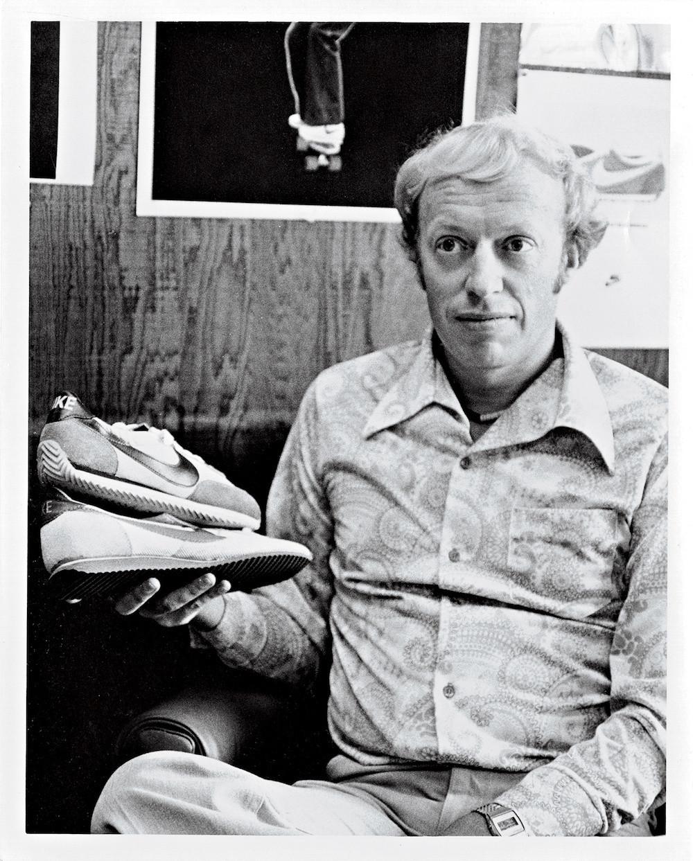 Photo de Phil Knight en noir et blanc avec une paire de Nike