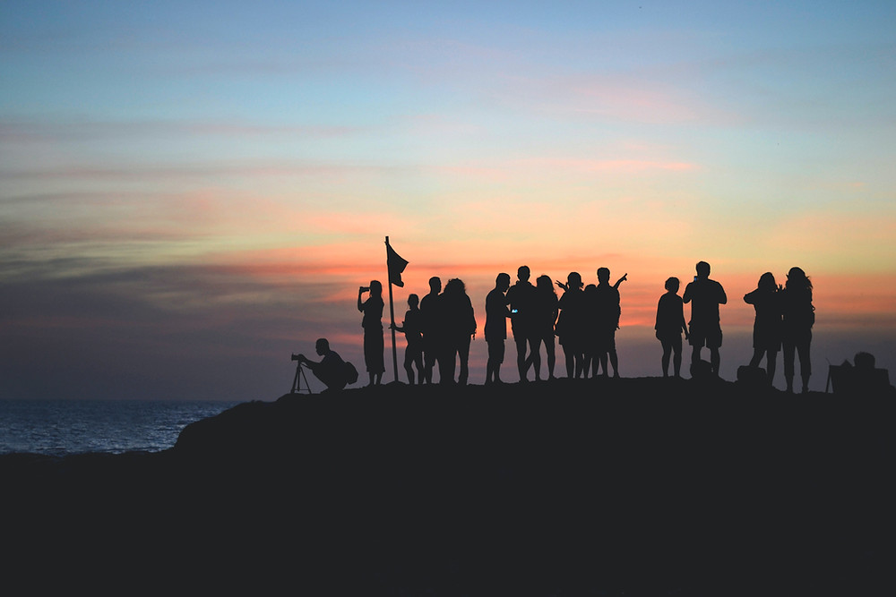 Groupe de personnes en train d'admirer un lever de soleil et de le photographier