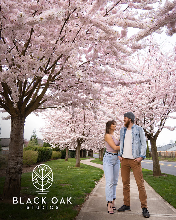 The owners Hannah and Jake posing outside in front of cherry blossoms.
