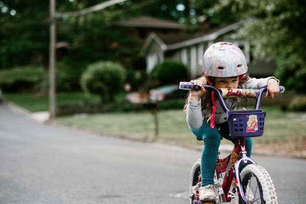 Young girl riding her bike. Photographed outdoors and on location by Charlotte Lifestyle & Day In The Life Photographer Jennifer A Steiger of Jennifer Ann Photography